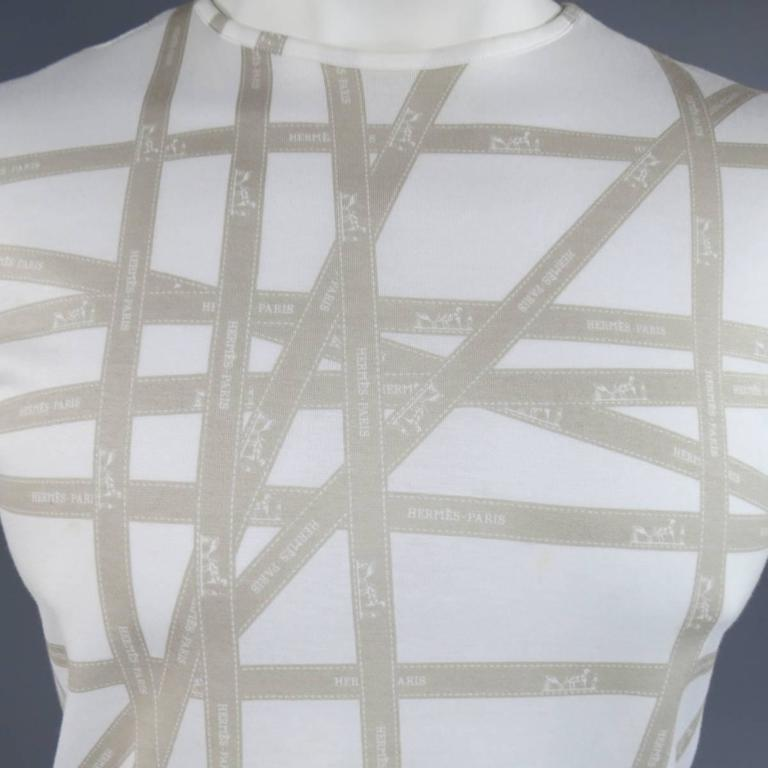Vintage HERMES tee shirt in a light weight, semi sheer, white cotton with a crewneck, short sleeves, and all over taupe beige Hermes Bolduc ribbon print. Small stain shown in detail shot. Made in Italy.   Good Pre-Owned Condition. Marked: XL