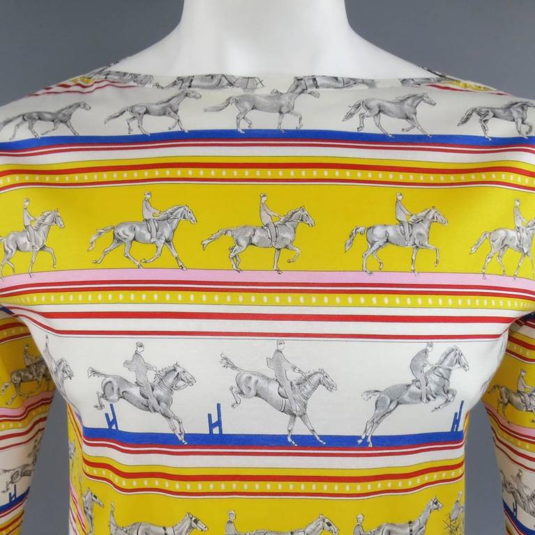 """Rare vintage HERMES """"Sequences"""" long sleeve boat neck T-shirt in a light weight, semi sheer cotton jersey in an all over cream, yellow, pink, red, and blue striped print with various gray horse riders. Made in Italy.   Excellent Pre-Owned"""