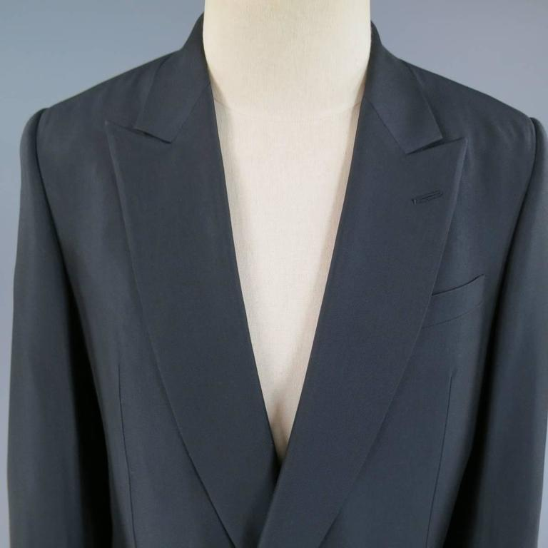 This chic BALENCIAGA double breasted sport coat comes in a deep midnight navy wool rayon blend twill with a sheen to it and features a pointed peak lapel, navy buttons, double flap pockets, and single vented back. Made in Italy. Retails at