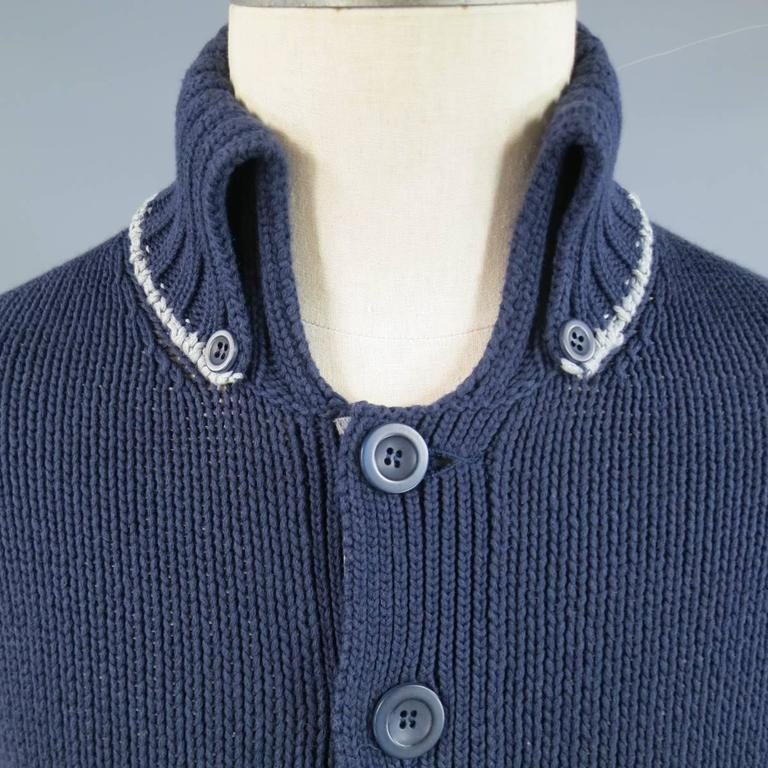 Unique BRUNELO CUCINELLI cardigan in a navy cotton blend medium weight navy blue knit with a button up silver gray lined closure, patch pockets, and a high ribbed button down collar with silver trim. Made in Italy.