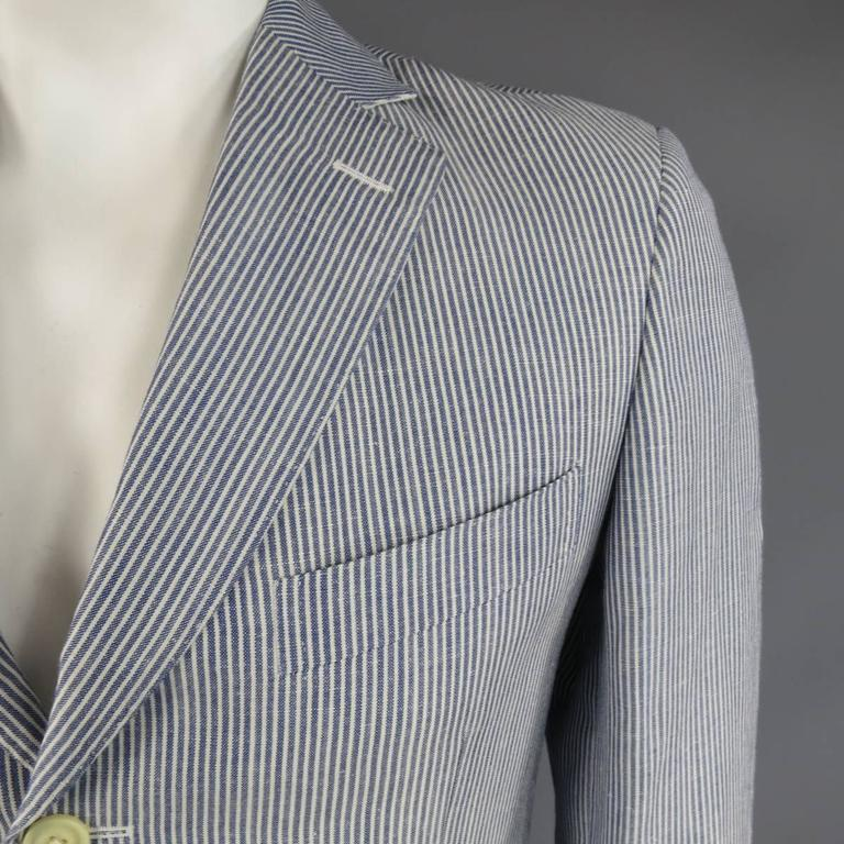 PAL ZILERI Sport Coat consists of linen/wool material in a light blue color tone. Designed in a notch lapel collar, 3-button front, top pocket square and bottom flaps. Detailed stripe pattern with white accent, 4-button sleeve cuffs and double back