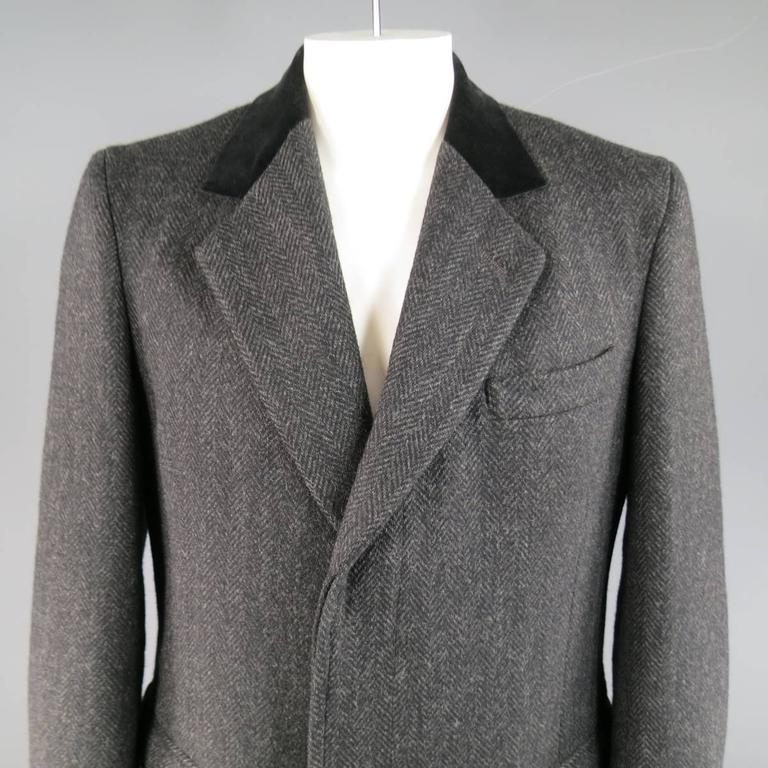 Classic winter coat by BARNEY'S NEW  YORK in a charcoal gray Herringbone print heavy wool featuring a notch lapel, black velvet collar, hidden placket button up closure, double flap pockets, and single vented back. Made in USA.   Excellent