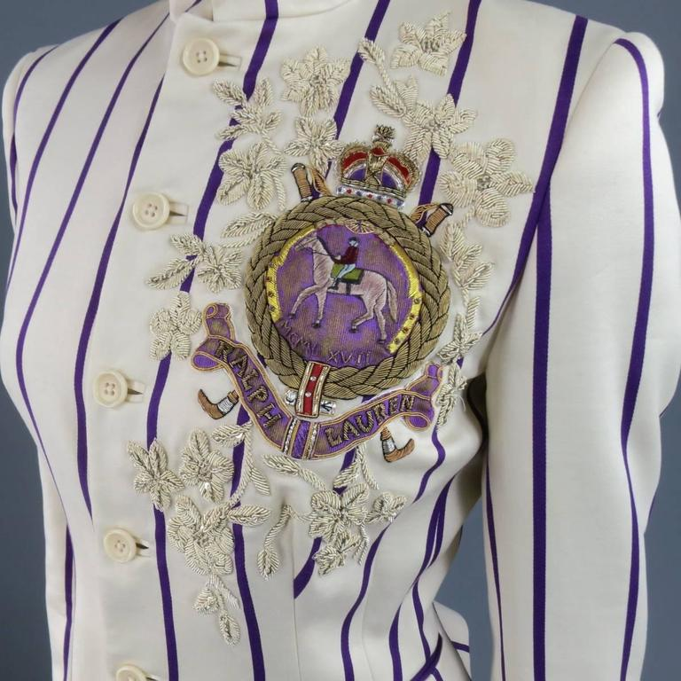 This gorgeous RALPH LAUREN COLLECTION cropped equestrian style jacket comes in a cream cotton matte satin fabric with violet purple stripes and features a stand up collar, tailored silhouette, ruffled fishtail back, and stunning embroidery and