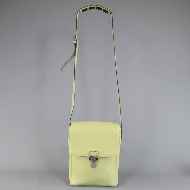 Vintage BALLY bag in a unique mint greenish tone beige textured leather featuring a flap with silver tone buckle, double storage compartments, and shoulder strap with rubber grip panel. In excellent condition with exception of the buckle being