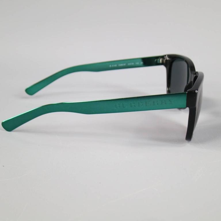 BURBERRY Sunglasses consists of acetate and metal material in a black and teal color tone. Designed in a classic sport lens style, metallic teal temples with engraved
