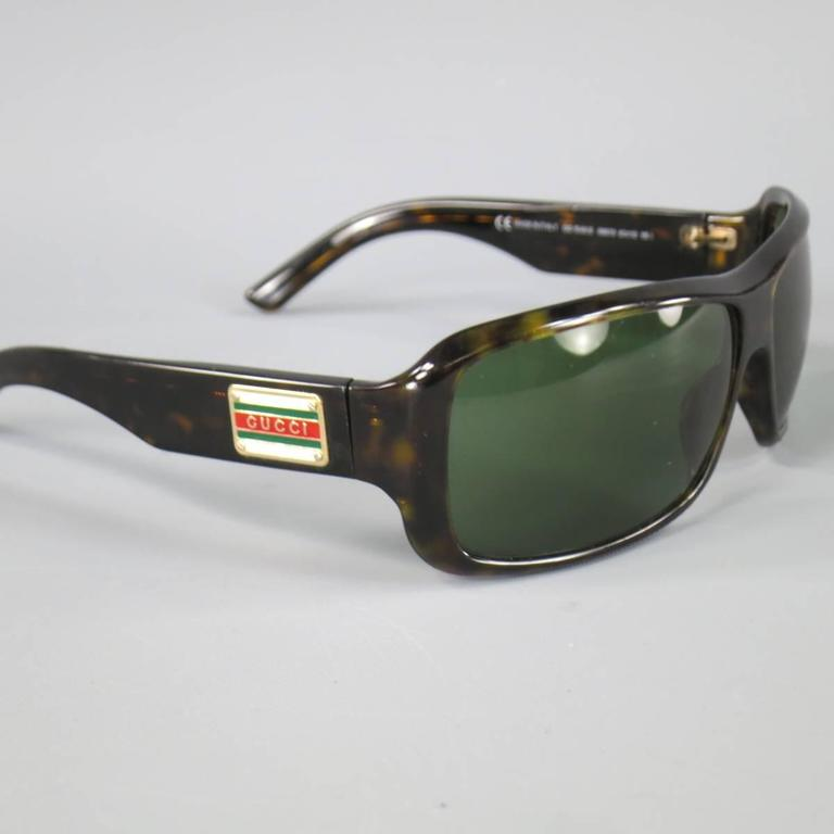 Vintage GUCCI sunglasses in a dark brown tortoiseshell acetate featuring a square green lens and thick arms with gold retro Gucci logo. Minor wear. As-Is. Made in Italy.   Fair Pre-Owned Condition. Marked: 1548 08670 63 12 115/   63 x 12 x 115 mm