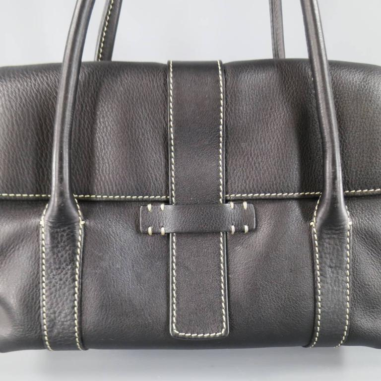 "LORO PIANA ""Dandy"" shoulder bag in a black textured leather featuring double covered top handle straps, fold over top with tab closure, internal zip pocket, and contrast stitching throughout. Internal wear and mild aging of leather. Made"