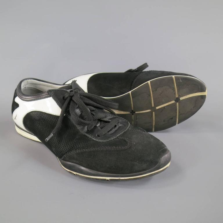 SALVATORE FERRAGAMO Sneakers consists of suede material in a black and white color tone. Designed in a round toe front, contrast white trimming along back. Detailed with rubber sole. Made in Italy.   Good Pre-Owned Condition Marked Size: EE 7