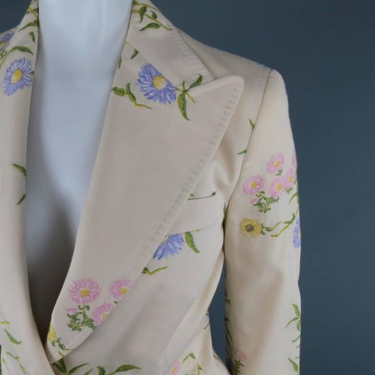 DOLCE & GABBANA blazer in a khaki beige cotton blend with all over pink, purple, and yellow daisy floral embroidered print throughout featuring a wide peak lapel with top stitching, simulated flap pockets, and dark silver tone engraved buttons with