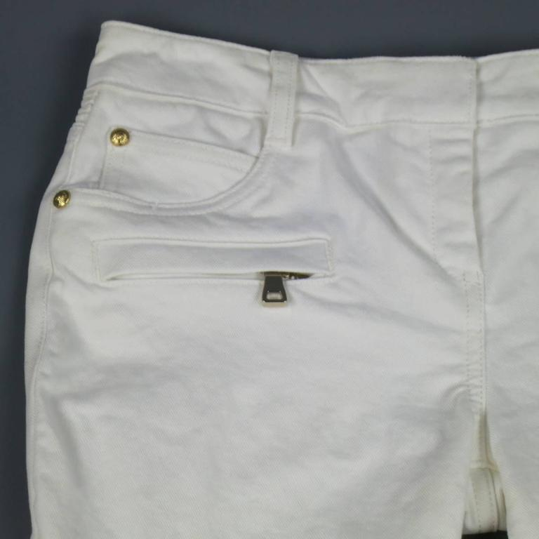 Signature BALMAIN motorcycle jeans in a white cotton twill featuring  a low rise, double zip frontal pockets, simulated knee pads, ribbed panels, and zip leg closure. Retails at $1200.00.   Excellent Pre-Owned Condition. Marked: 36   Measurements: