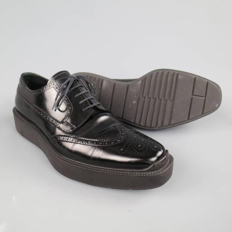 Chic PRADA dress shoes in aa smooth semi patent lather featuring a squared off pointed toe with wingtip, perforated brogue details throughout, and thick rubber platform sole. Made in Italy.   Excellent Pre-Owned Condition.   Outsole: 13 x 4.75