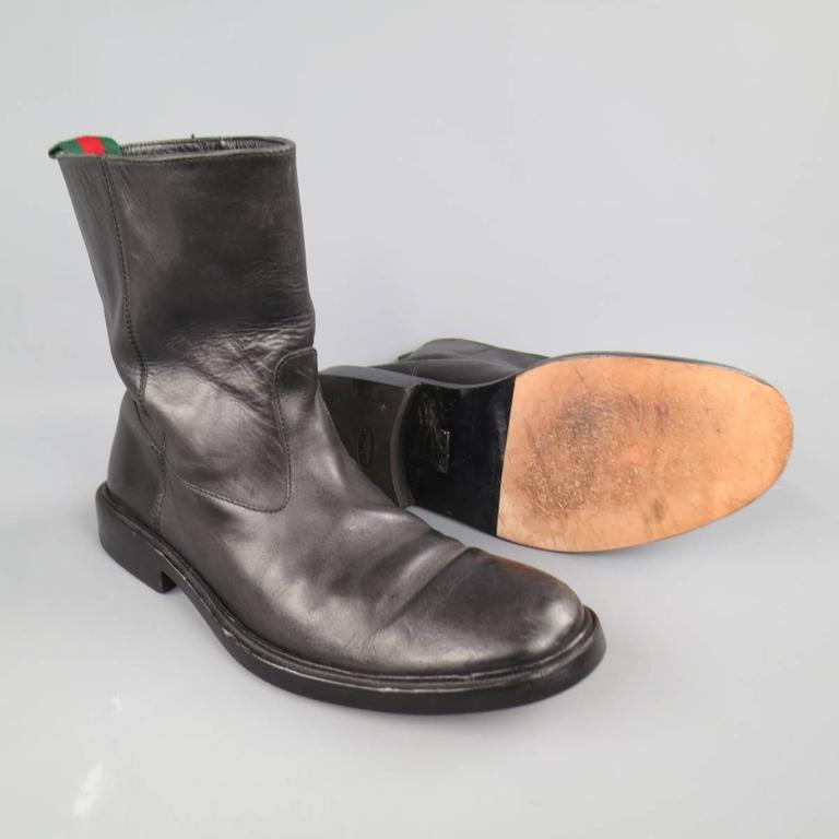 Classic GUCCI pull on biker style boots in black leather featuring a round toe,medium  tall shaft, and signature green and red striped webbing pull tab on back. Made in Italy.   Good Pre-Owned Condition. Marked: UK 10 D   Outsole: 12.75 x 4.75