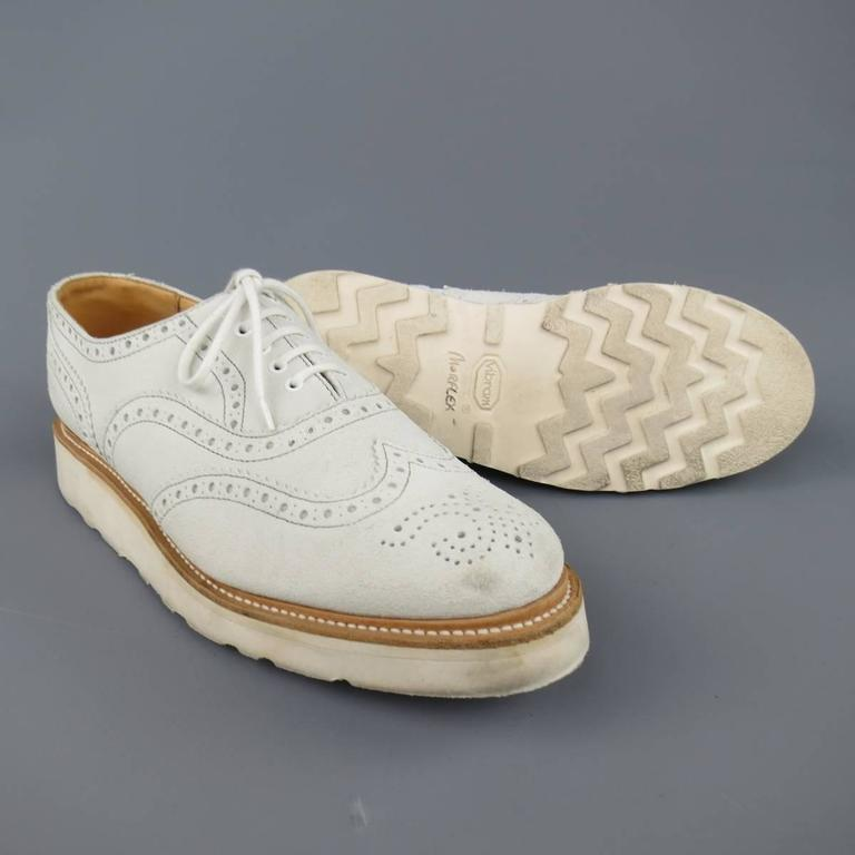 HERITAGE RESEARCH brogues in an off white suede featuring a round toe with wingtip, perforated brogue details throughout, and thick Vibram sole. Wear throughout. Made in  England.   Good Pre-Owned Condition. Marked: UK 8   Outsole: 12 X 4 in. Sole: