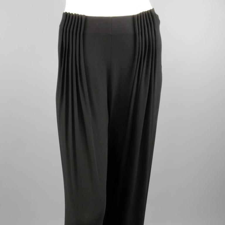 FENDI black rayon dress pants feature a wide leg with gathered pleats in the front with side zipper and hook and eye closure. Made in Italy.   Excellent Pre-Owned Condition. Marked: 40   Measurements:   Waist: 32 In. Rise: 9.5 In. Inseam: 34 In.
