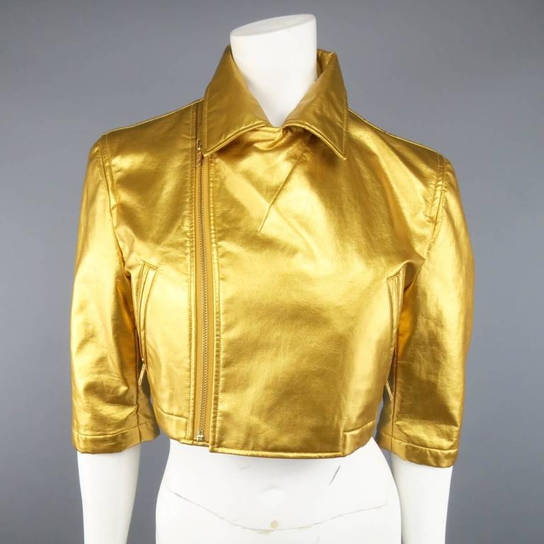 COMME DES GARCONS cropped biker style jacket in a metallic yellow gold vegan leather featuring a pointed collar with asymmetrical zip closure, slanted zip pockets, and three-quarter sleeves with zip opening. Tag Ripped and small imperfection on