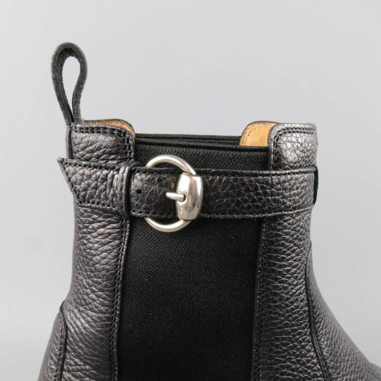 GUCCI ROYER Boot consists of leather material in a black color tone. Designed in a classic slip-on style, adjustable top buckle with back tab. Round toe front in a pebble texture. Rubber grip sole. Made in Italy.   Excellent Pre-Owned Condition.