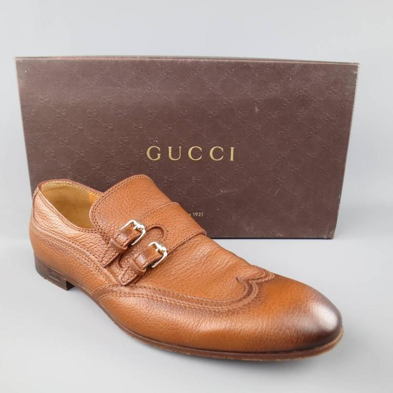 GUCCI Loafers consists of leather material in a tan color tone. Designed in a double monk-strap with silver buckles. Tone-on-tone stitching, burnish color pattern. Leather lining and sole. Comes with original box and cloth bag. Made in Italy.   Good