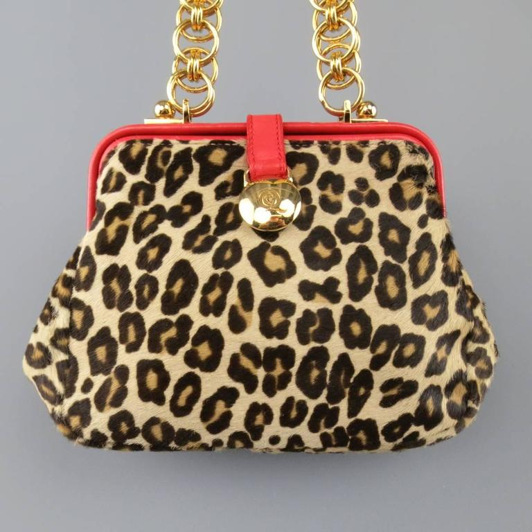 ALEXANDER MCQUEEN purse in a beige cheetah leopard print ponyhair leather features bright red leather details yellow gold tone hoop chain shoulder strap and snap closure. Minor Wear.   Good Pre-Owned Condition.   Measurements:   Length: 9 in. Width: