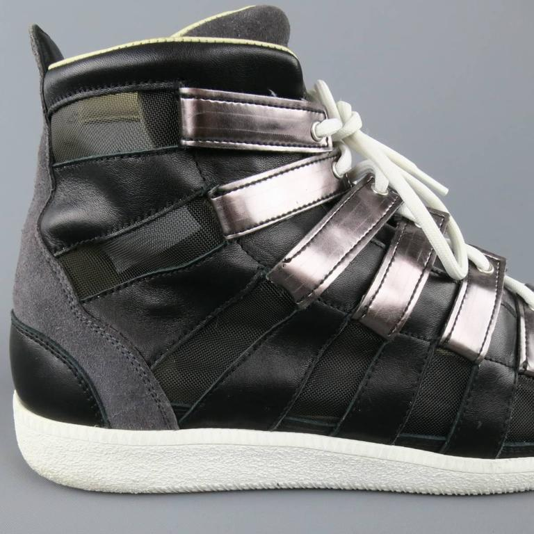 MAISON MARTIN MARGIELA high top sneakers feature black leather and mesh stripe paneled sides, charcoal suede toe, smoke silver metallic leather tab lace up front, and white rubber sole. Made in Italy.   Excellent Pre-Owned Condition. Marked: IT