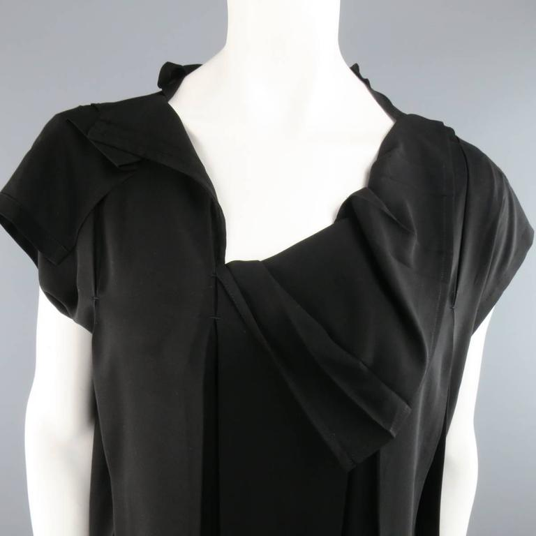 ISSEY MIYAKE black chiffon blouse features asymmetrical pleating details throughout and mock cap sleeves. Made in Japan.   Excellent Pre-Owned Condition. Marked: 3   Measurements:   Shoulders: 35 In. Bust: 49 In. Length: 25 In.