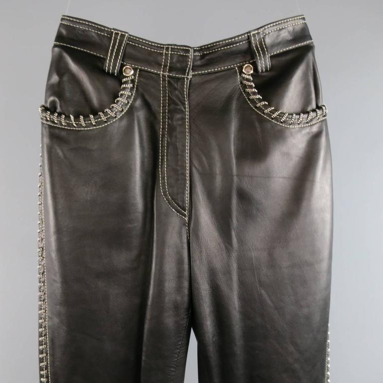 Vintage GIANNI VERSACE black leather pants feature all-over white white stitching and chain link detailing, zipper fly closure, Medusa head rivets, zipper detailing at the hems and zipper flap pockets in the back. Partially lined. With Tags. Made in