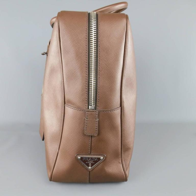 Classic rectangular PRADA briefcase in a light brown Seffiano textured leather featuring a thick silver tone zip top closure with side lock, double covered top handles, luggage tag, and internal storage. Wear throughout. with dust bag. As-Is. Made