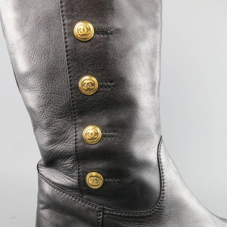 Vintage CHANEL knee high pull on boots in a smooth black leather featuring a rounded point toe and simulated gold tone CC button up sides. Minor wear and imperfection on toe. As-Is. Made in Italy.   Fair Pre-Owned Condition. Marked: IT 41   Outsole: