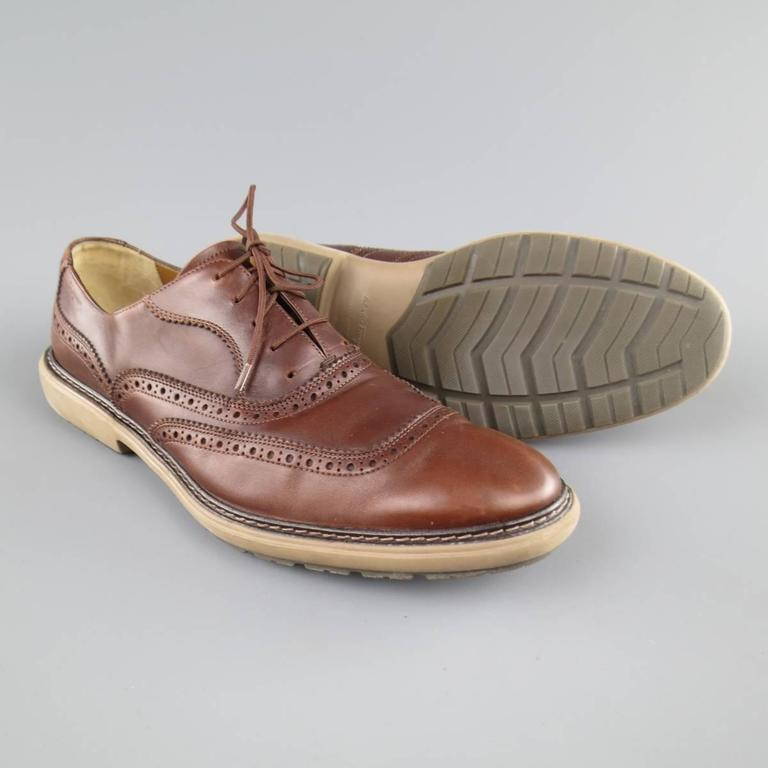 SALVATORE FERRAGAMO lace ups in a tan brown leather featuring perforated brogue details throughout and a tan rubber sole. Wear throughout leather. Made in Italy.   Fair Pre-Owned Condition. Marked:11   Outsole: 13 x 4.75 in.