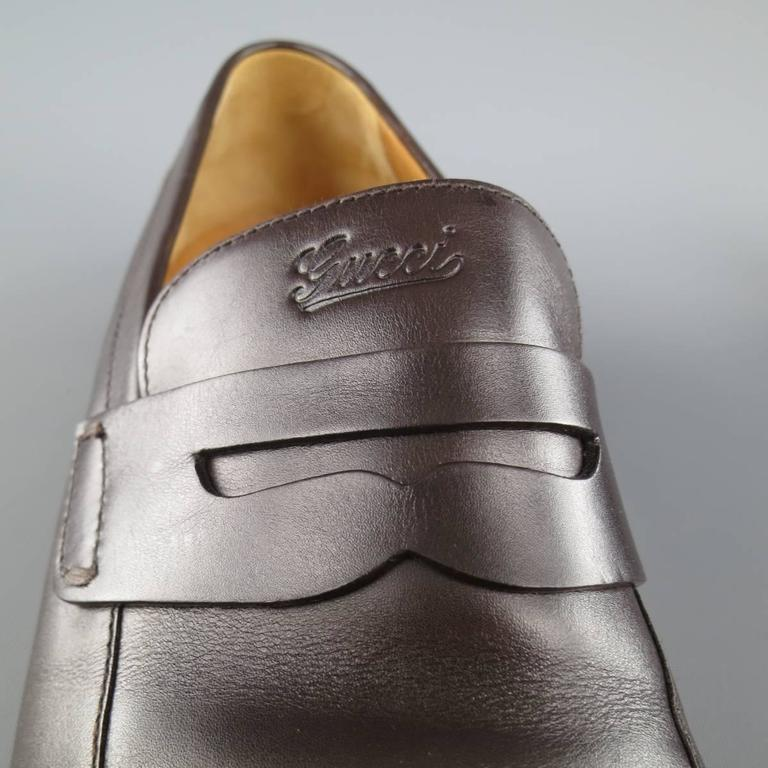 441873e0f GUCCI penny loafers in a rich chocolate brown leather with a pointed apron  toe and cursive