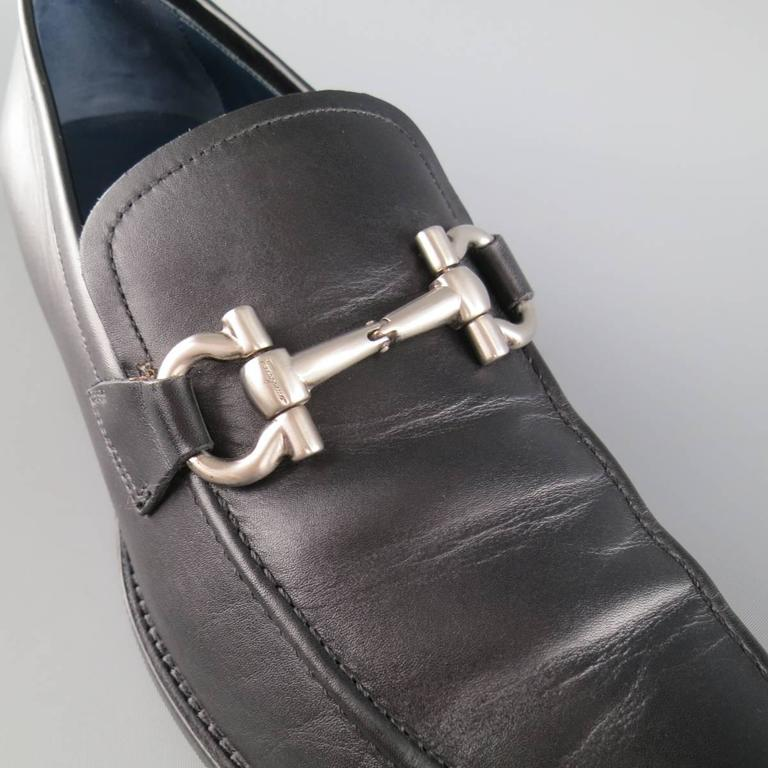 SALVATORE FERRAGAMO Loafers consists of leather material in a black color tone. Designed with signature double-gancio buckle in silver tone and top tone-on-tone stitching. Leather sole with rubber heel. Made in Italy.   Good Pre-Owned