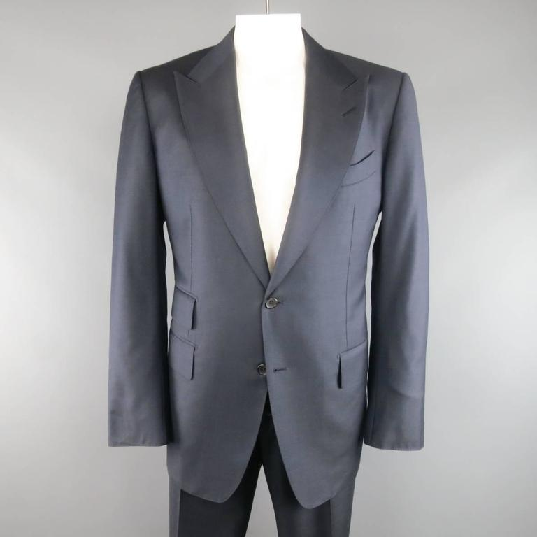 TOM FORD suit comes in a navy blue wool and includes a two button sport coat with peak lapel, three flap pockets, and functional button cuffs with matching adjustable tab waistband dress pants with cuffed hem. Made in Italy.   Excellent Pre-Owned