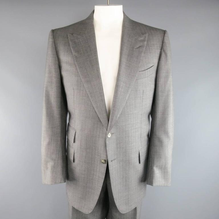 Tom Ford two piece suit comes in a gray herringbone wool fabric and includes a two button, peak lapel sport coat with flap pockets, and functional button cuffs with matching flat front, adjustable tab waistband dress pants. Made in Italy.  Excellent