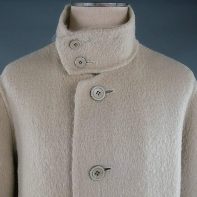 ISSEY MIYAKE Coat consists of wool blend material in a cream color tone. Designed in a oversize style, button-up front and bottom patch pockets. Detailed with a high collar button closure. Fuzzy texture with cropped sleeves. Made in Japan.