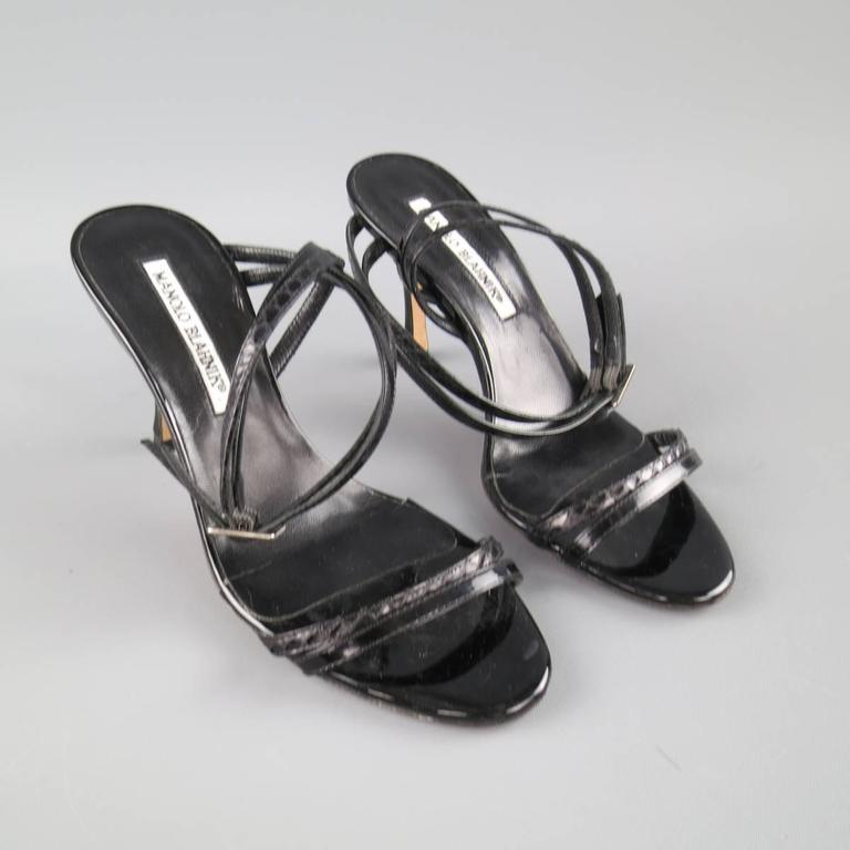 MANOLO BLAHNIK sandals come in a high gloss black patent leather with snake skin details and feature a double skinny toe strap, covered stiletto heel, and asymmetrical wrapped ankle straps. Made in Italy.   Good Pre-Owned Condition. Marked:IT 36.5