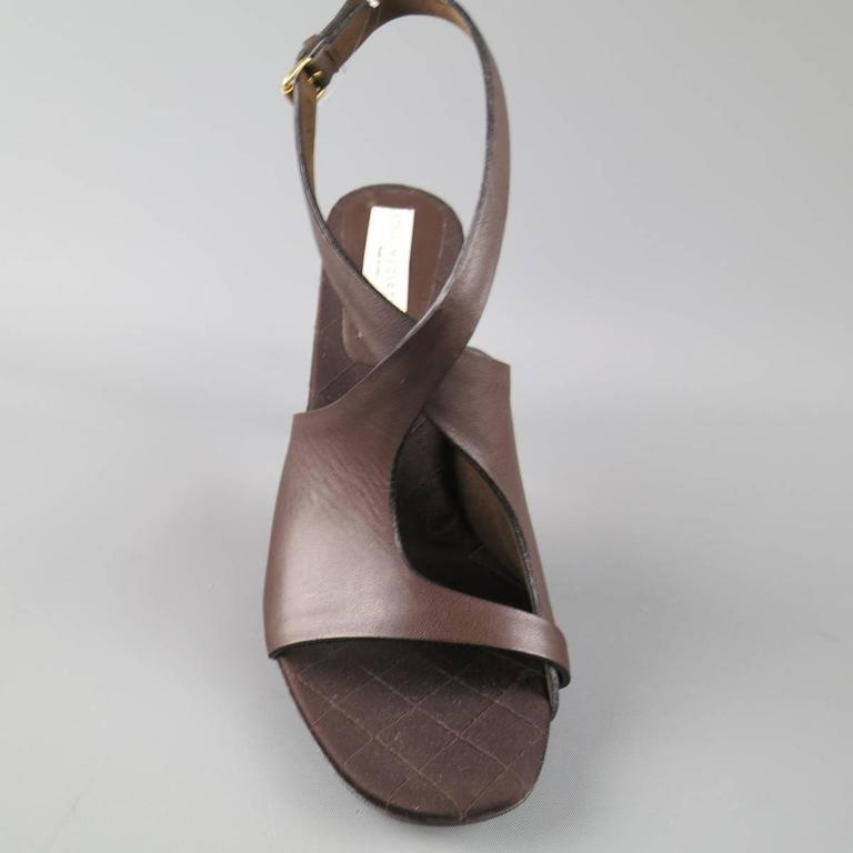 STELLA McCARTNEY sandals com in a deep chocolate brown vegan leather and feature a peep toe, thick cutout toe strap with crossed ankle straps, matte stiletto heel, and gold sole. Made in Italy.   Excellent Pre-Owned Condition. Marked:IT 40.5   Heel: