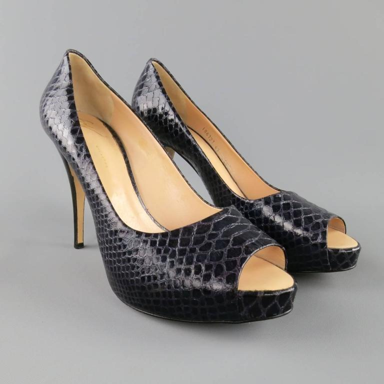 GIUSEPPE ZANOTTI pumps come in a deep violet purple snakeskin leather and feature a peep toe, concealed platform, and stacked stiletto heel. Made in Italy.   Excellent Pre-Owned Condition. Marked: IT 41   Heel: 4.75 in. Platform: 1 in.   Web ID: