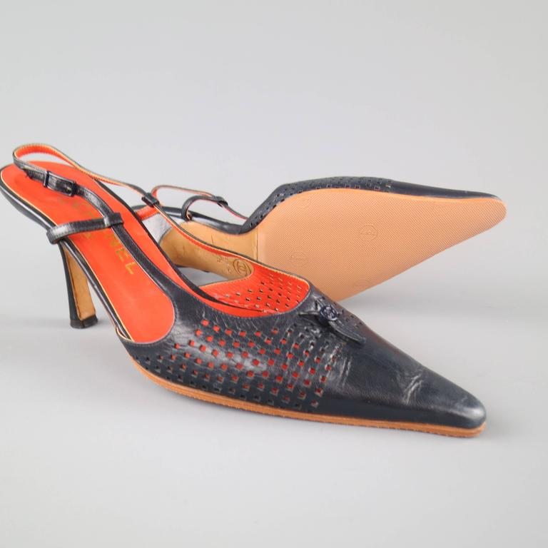 Vintage CHANEL slingback pumps in navy blue leather featuring a pointed toe with perforated cutouts and emblem detail, red interior, and covered stiletto heel. With box. Made in Italy.   Good Pre-Owned Condition. Marked: IT 37.5   Heel: 3.5