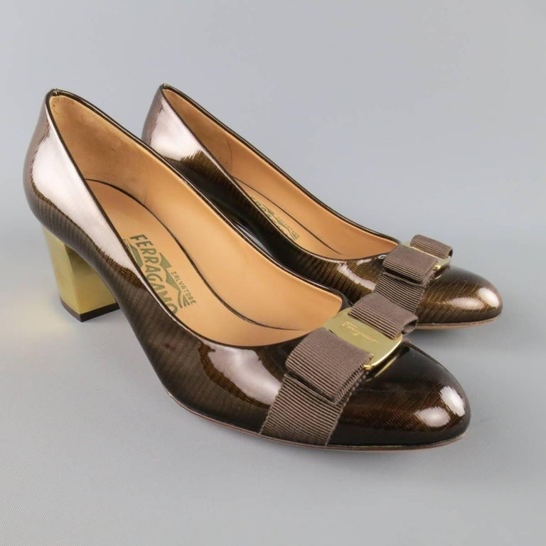 SALVATORE FERRAGAMO pumps come in a glossy brown lizard patent leather and feature a gold tone engraved plaque with ribbon bow and metallic gold tone chunky heel. Never worn but minor imperfections. Made in Italy.   Excellent Pre-Owned