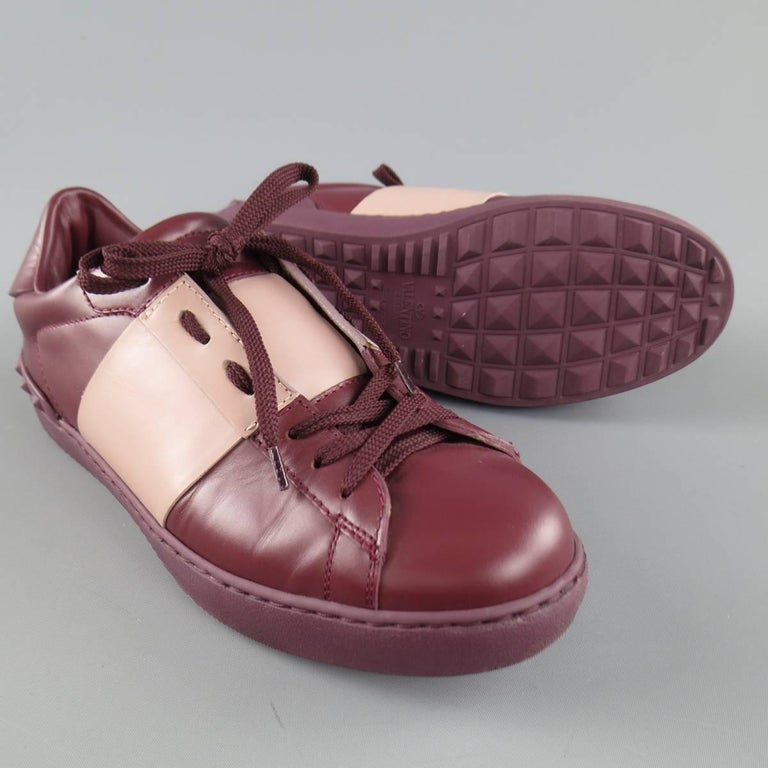 "VALENTINO ""Rockstud"" sneakers come in burgundy smooth leather with a mauve stripe and feature a stud textured rubber sole. Minor wear. Made in Italy.   Excellent Pre-Owned Condition. Marked: 40 1/2   Web ID: 83413"