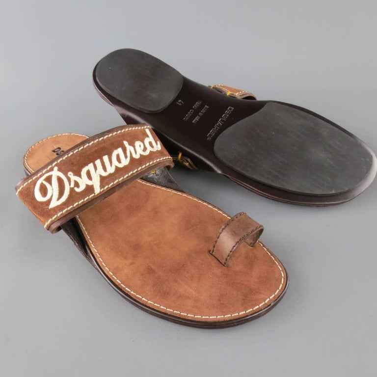 DSQUARED2 sandals feature a thick tan brown suede strap with cream embroidered logo and leather toe strap. Made in Italy.   Excellent Pre-Owned Condition. Marked: 41   Web ID: 83156
