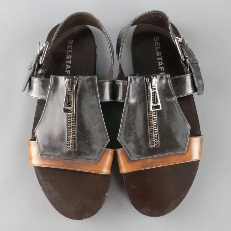 BELSTAFF sandals come in two tone distressed look tan and charcoal patent leather and feature a thick geometric patchwork statement front with gunmetal tone zipper and back strap with buckle. Made in Italy.   Good Pre-Owned Condition. Marked: