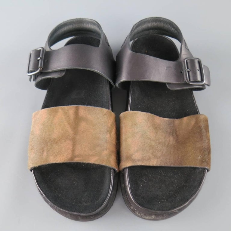 ALLSAINTS SPITFEILDS sandals feature a thick light brown printed ponyhair leather toe strap, black leather ankle harness with black hardware, and thick sole. Made in Portugal.   Brand New. Marked: 44   Web ID: 79643