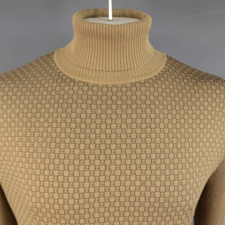 Golden tan khaki ribbed silk print turtleneck sweater by GUCCI featuring a frontal brown G monogram print panel. Made in Italy.   Excellent Pre-Owned Condition. Marked: L   Measurements:   Shoulder: 21 in. Chest: 48 in. Sleeve: 27 in. Length: 28
