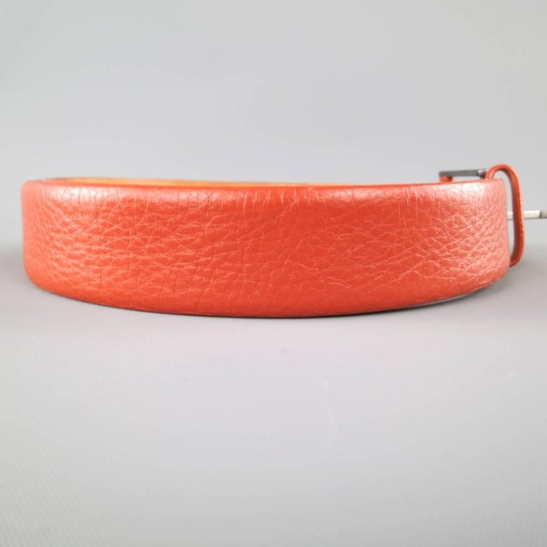 GIORGIO ARMANI dress belt features a rich burnt orange pebbled leather strap with a smoke silver tone, leather detailed, buckle. Made in Italy.   Good Pre-Owned Condition. Marked: 48   Length: 38.5 in. Width: 1.25 in. Fits: 32-36 in.  SKU: 84647