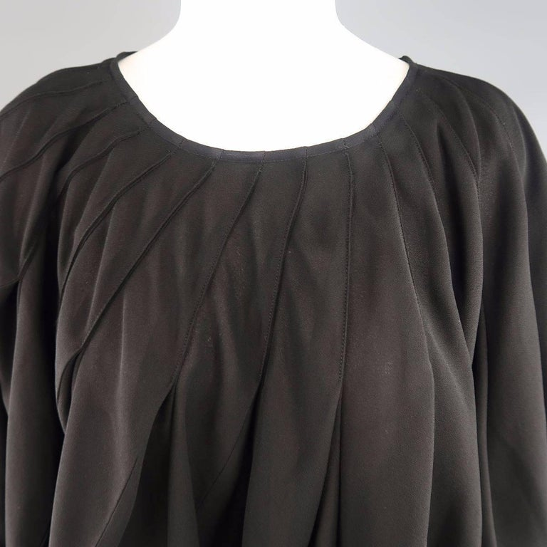 JUNYA WATANABE COMME des GARCONS poncho style bubble blouse comes in a black semi sheer crepe and features an all over pleated ruffle construction with side slits. Made in Japan.   Excellent Pre-Owned Condition. Marked: S   Measurements:   Shoulder: