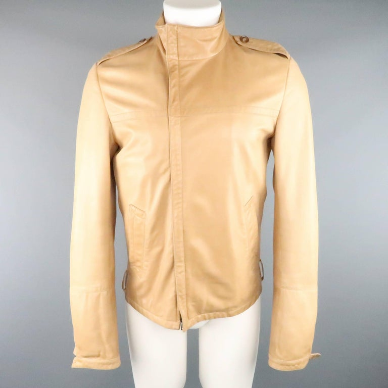 This GUCCI by TOM FORD circa 2000 jacket comes in a butter soft light tan leather and features an asymmetrical zip high collar, epaulets, slanted pockets, and tab cuff sleeves. Minor wear and missing belt and cuff hardware. As-Is. Made in Italy.
