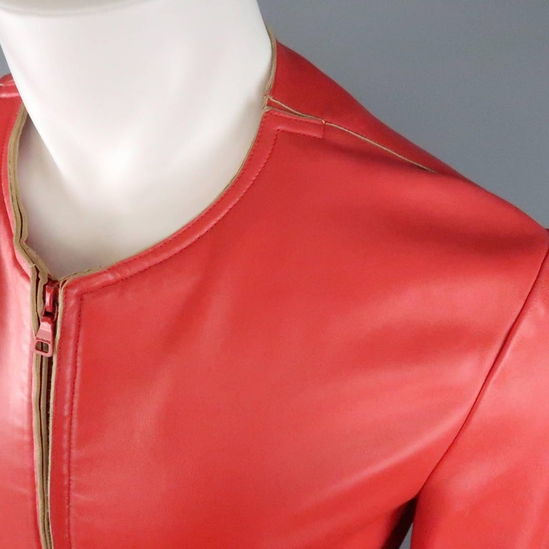 JIL SANDER jacket comes in a soft, light weight red leather and features a round, collarless neckline, red double zip front, slit pockets, and beige raw edge details. Some very small spots throughout leather. As-Is. Made In Italy.   Good Pre-Owned