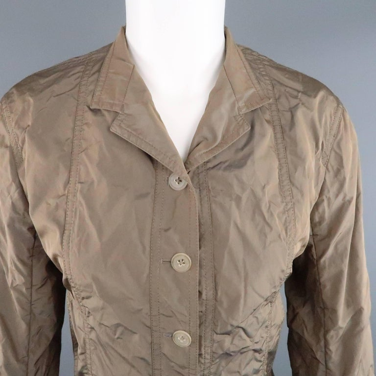 JIL SANDER sport coat comes in a light weight iridescent taupe taffeta and features a five button closure, slit pockets, and high collar. Made in Italy.   Excellent Pre-Owned Condition. Marked: (no tag)   Measurements:   Shoulder: 16 in. Bust: 36