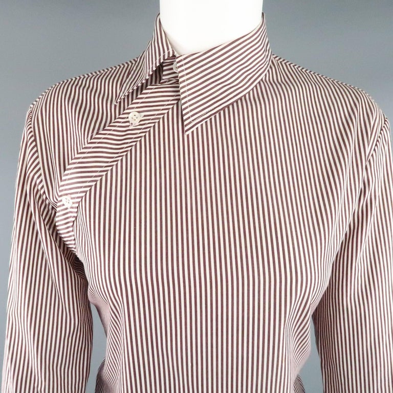 Avant garde dress top from rare early 1990's label COPPERWHEAT BLUNDELL comes in burgundy and white striped cotton and features a pointed collar, asymmetrical button closure, and French cuffs. Small discolorations shown in detail shots. As-Is.  Made