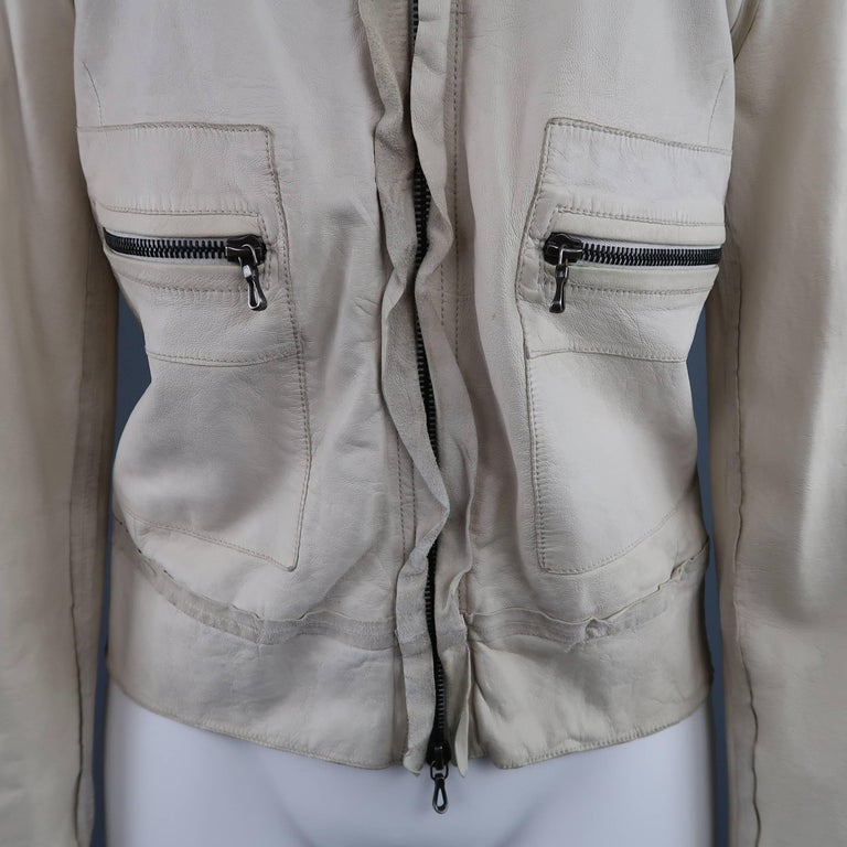 LANVIN leather jacket comes in a creamy off white leather and features a round, collarless neckline, epaulets, zip patch pockets, and zip closure with ruffled trim. Minor wear throughout leather. Spring 2010. Made in Italy.   Good Pre-Owned